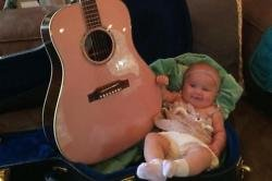 River Rose sitting next to the guitar
