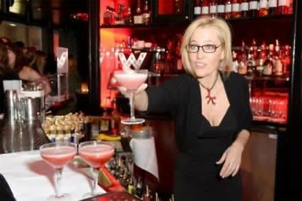 Gillian Anderson serving a W London's special Glitte(RED) cocktail at the W London and (RED) World AIDS Day Fundraising Party at the Wyld bar in centr