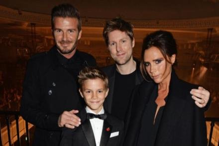 Romeo Beckham poses with Christopher Bailey and his parents David and Victoria Beckham at the 'From London with Love' launch